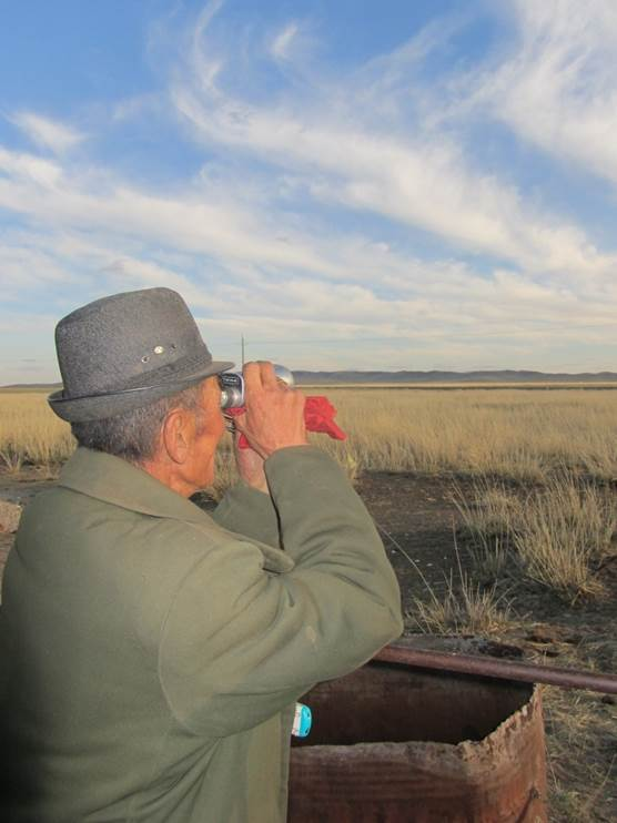 A telescope is an essential tool for herders. Damrin is watching the sheep through his telescope.