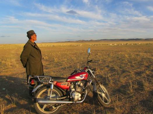 Damrin and his favourite motorbike. He said that he has not ridden a horse for many decades. Not far a way, his sheep are grazing peacefully.
